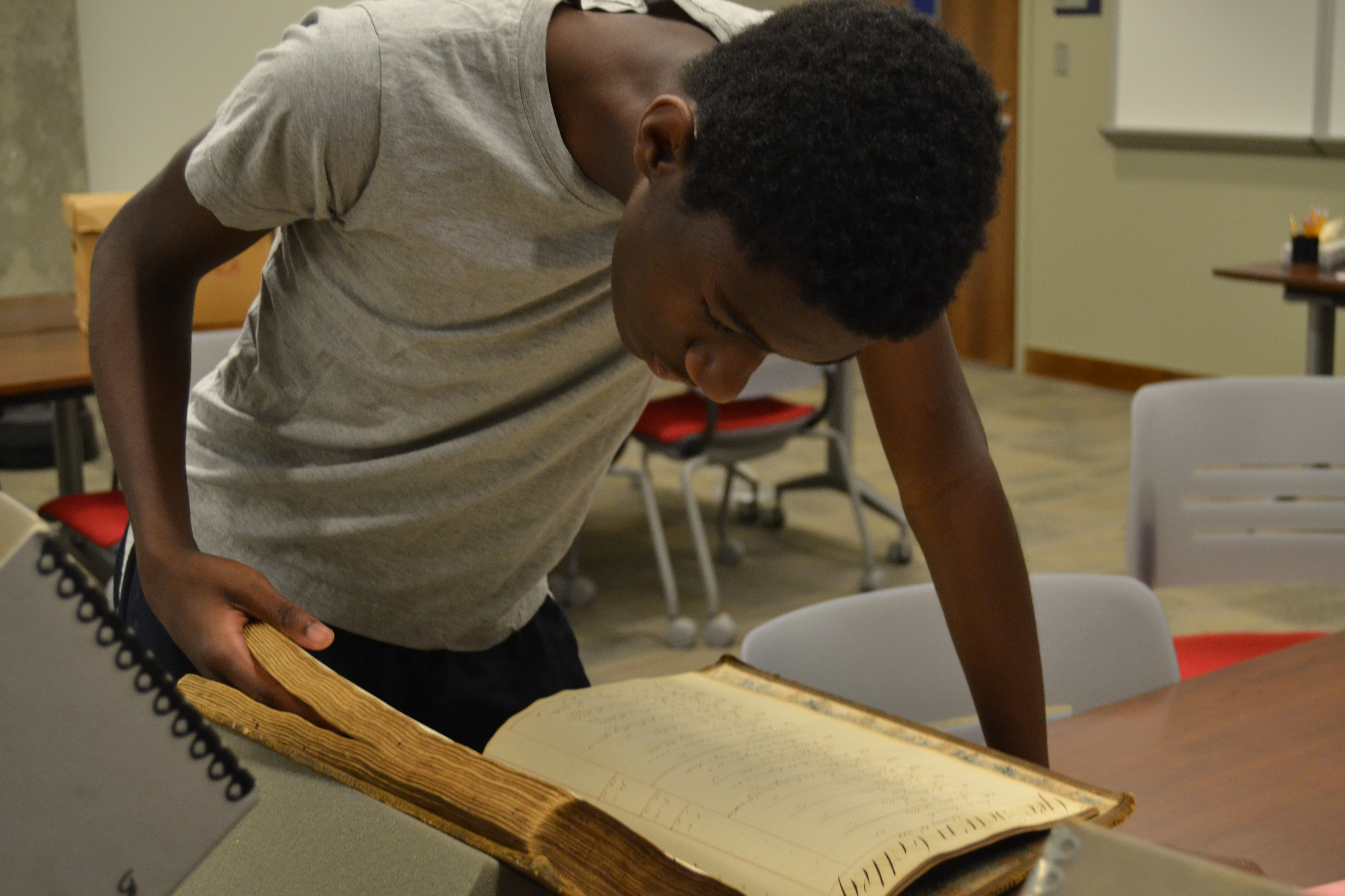 A student looks through a historical ledger in the Georgetown University archives.