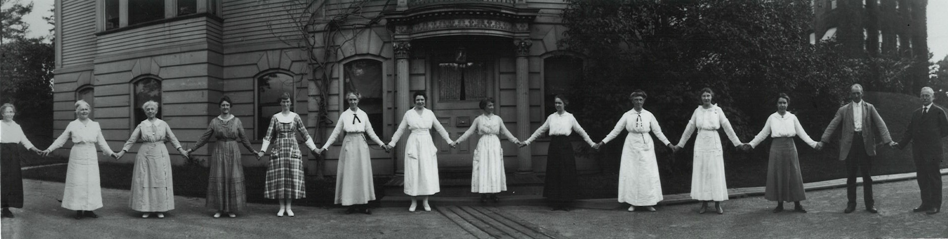"1918 black-and-white photograph of the Harvard ""computers"" holding hands and standing in a line like paperdolls."