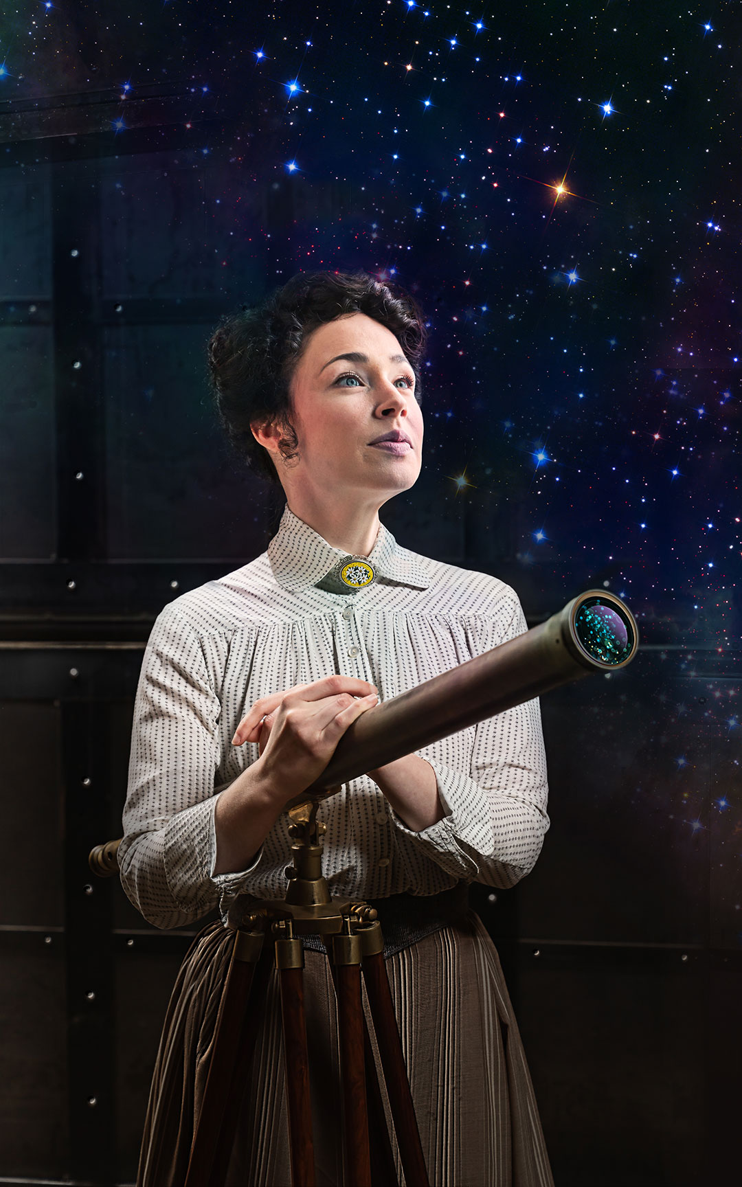 A woman wearing a white, collared Victorian blouse and high-waisted skirt stands behind a telescope looking wistfully into the sky.