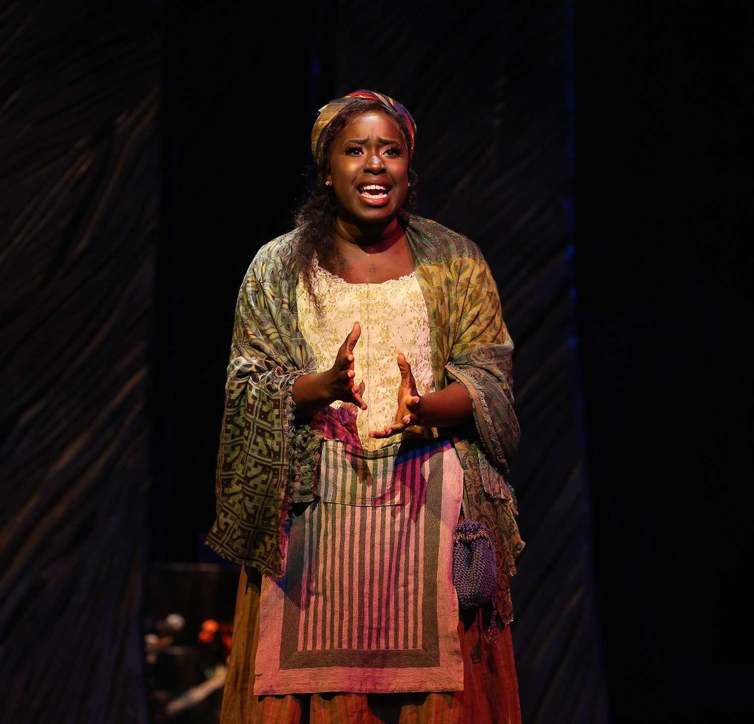 Baker's Wife stands and sings. She wears a corseted top, a brightly patterned scarf of reds, blues and yellows on her head, and an ankle-length yellow skirt