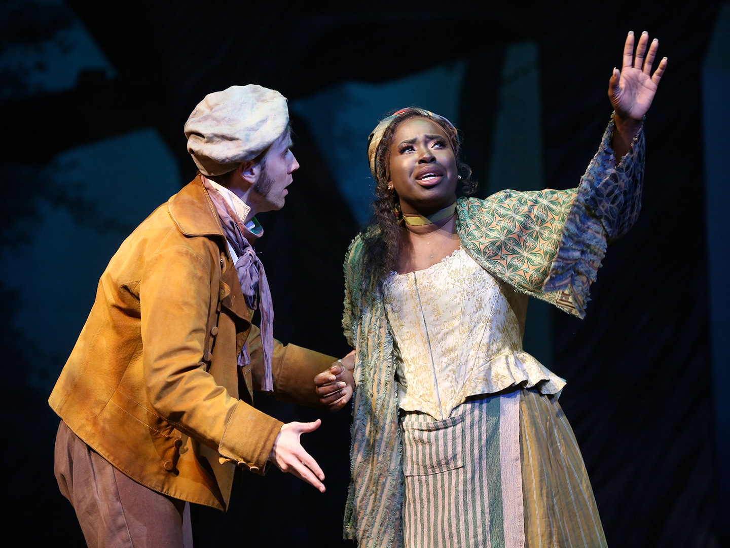 The Baker, wearing a yellow waistcoat, brown knee-length trousers and socks, green shoes and floppy baker's hat, stands next to an actress playing his wife. She wears a corseted top, a brightly patterned scarf of reds, blues and yellows on her head, and an ankle-length yellow skirt. He stands bewildered with mouth open while she looks to the skies with her hand extended.