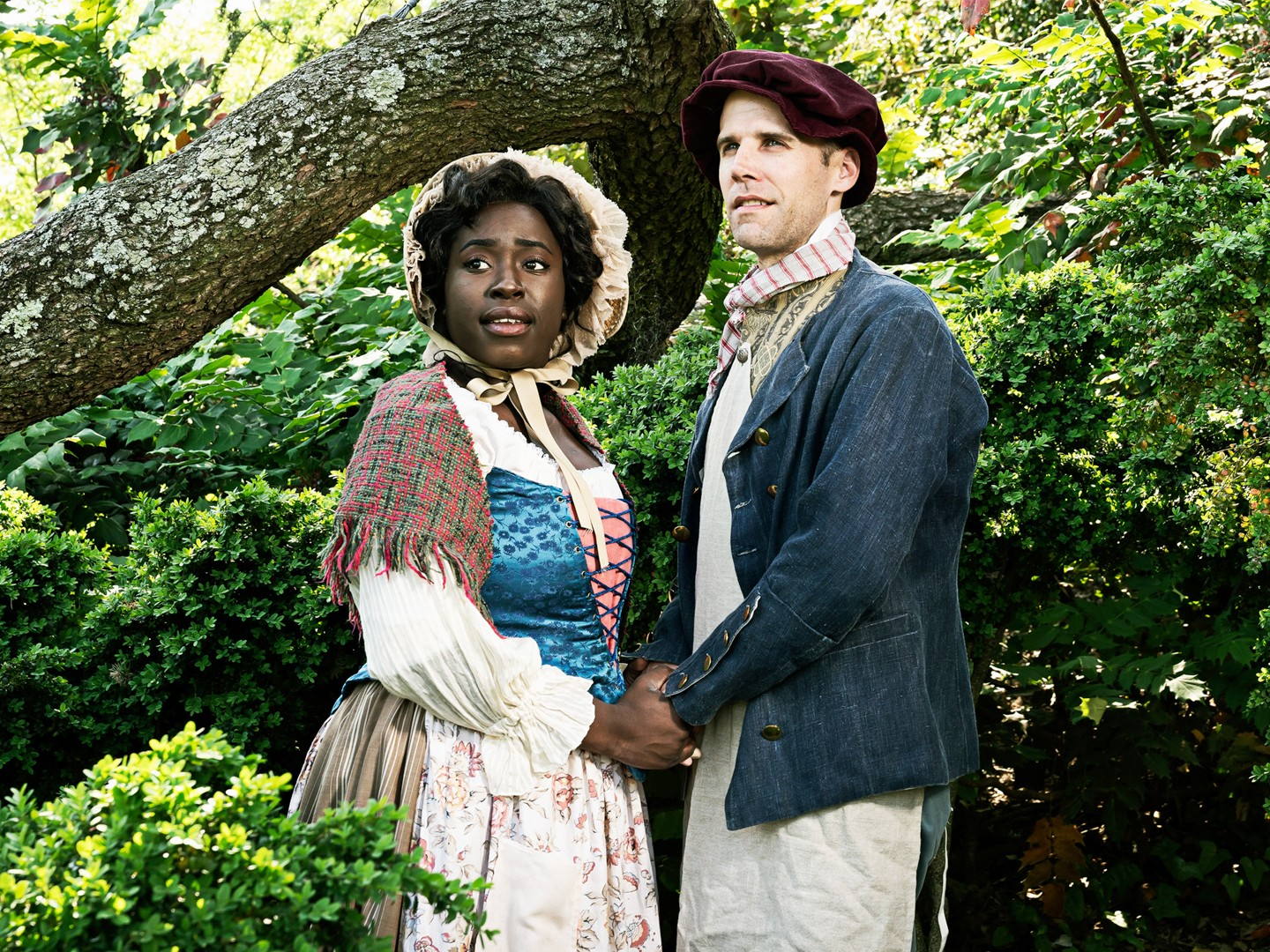 A black woman and white man hold hands in a forest. They are dressed like poor 18th-century fairy tale characters.