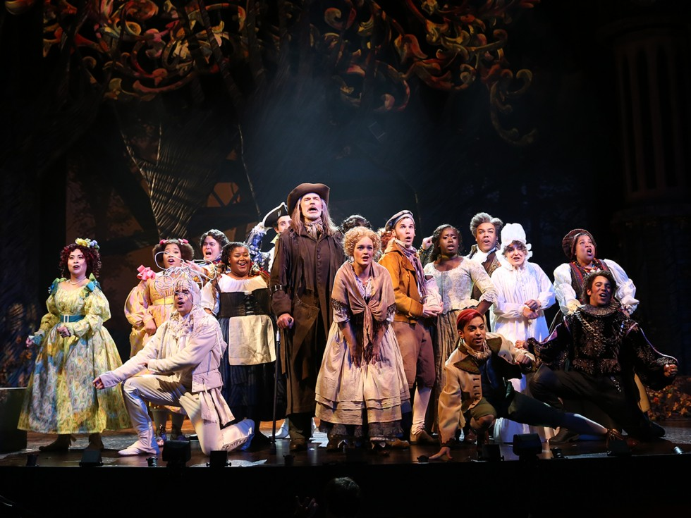 """At the front of the set, the cast of """"Into the Woods"""" stands or kneels in their fairy-tale costumes. Cinderella is in the center wearing her rags, Little Red Ridinghood and Milky White stand to the left, and Jack and his mother to the right. Cinderella's stepsisters are there—now blinded, they wear small dark glasses and hold canes. The baker and his wife, Rapunzel's Prince and others all gather around."""