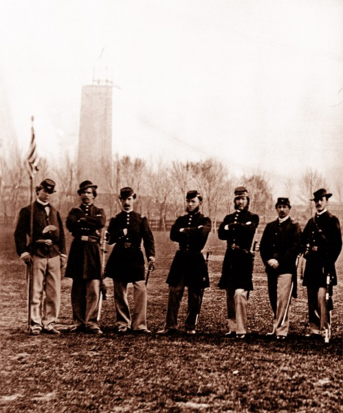 Seven Union soldiers in uniform pose with their muskets and an American flag on the National Mall. Behind them, the unfinished Washington Monument is seen.