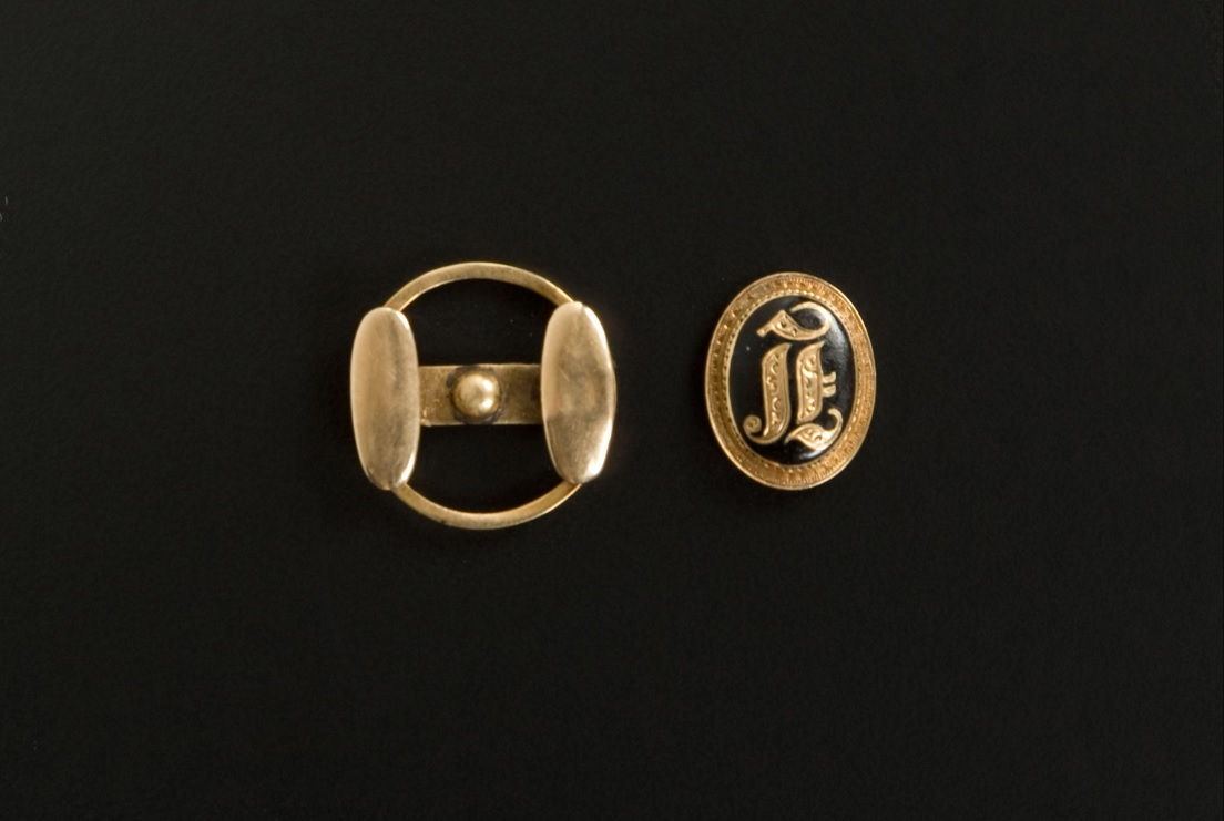 "A gold cufflink worn by Abraham Lincoln. The cufflink is oval with a black background and a large ""L"" printed in gold in the middle. The boarder of the cufflink is also framed in gold."