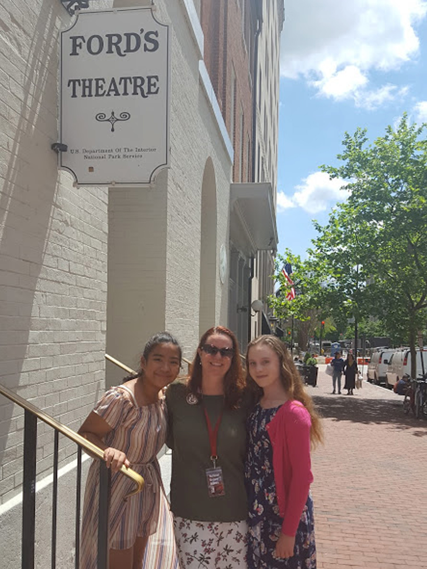 Teacher Karen Richey stands outdoors on the historic steps of Ford's Theatre flanked by two of her high school students.