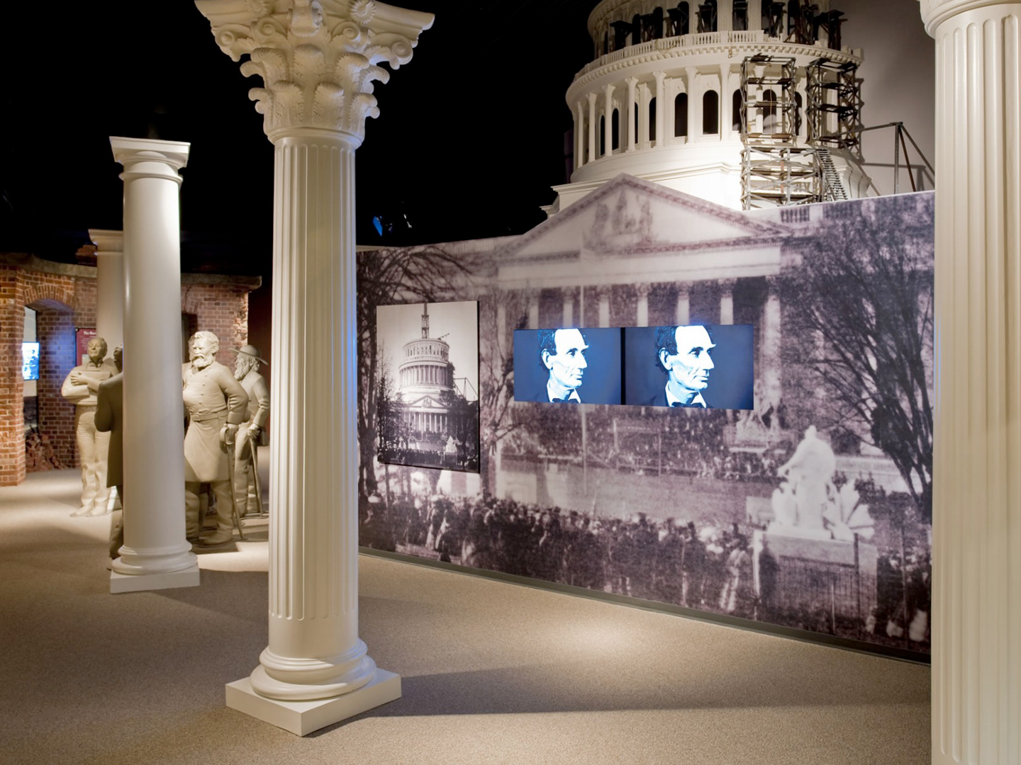 Inside the Ford's Theatre Museum, two television screens display close-up images of Abraham Lincoln's face. The screens are embedded in a display that is a large-scale photograph of the partially constructed U.S. Capitol dome taken during the Civil War. In front of the display are three white columns, designed to evoke the Capitol. Behind the display is a model of the partially constructed dome.