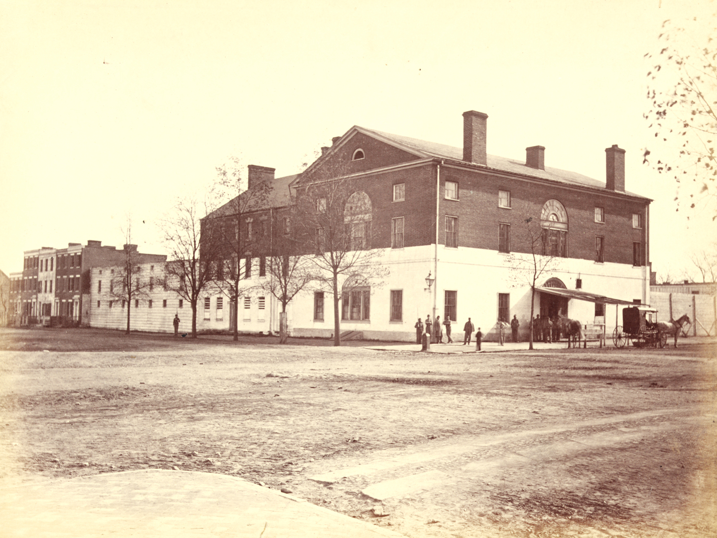 Sepia-toned photograph of three-story brick building with gabled roof and chimneys. Bottom half of building painted white, rest of building dark brick. Awning at front entrance, with people standing around front door.
