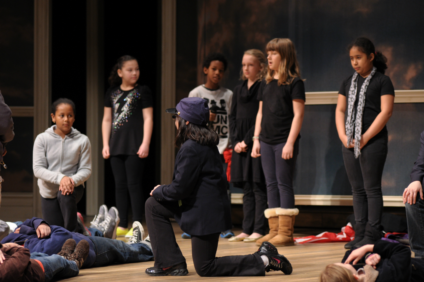 Ten or so students use their bodies to demonstrate text on the stage of Ford's Theatre. Some lay flat, some kneel, others stand and point. This is a class from D.C.'s Oyster Adams School (2012).