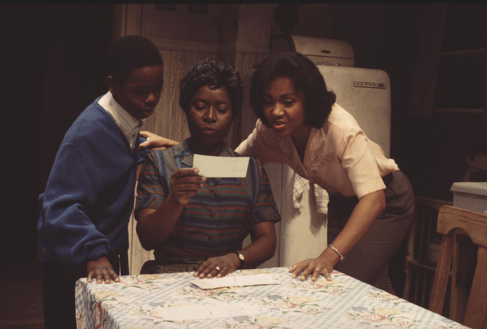 "Photo of three actors in the 1995 Ford's production of ""A Raisin in the Sun."" The three are huddled at a kitchen table looking at a piece of paper."
