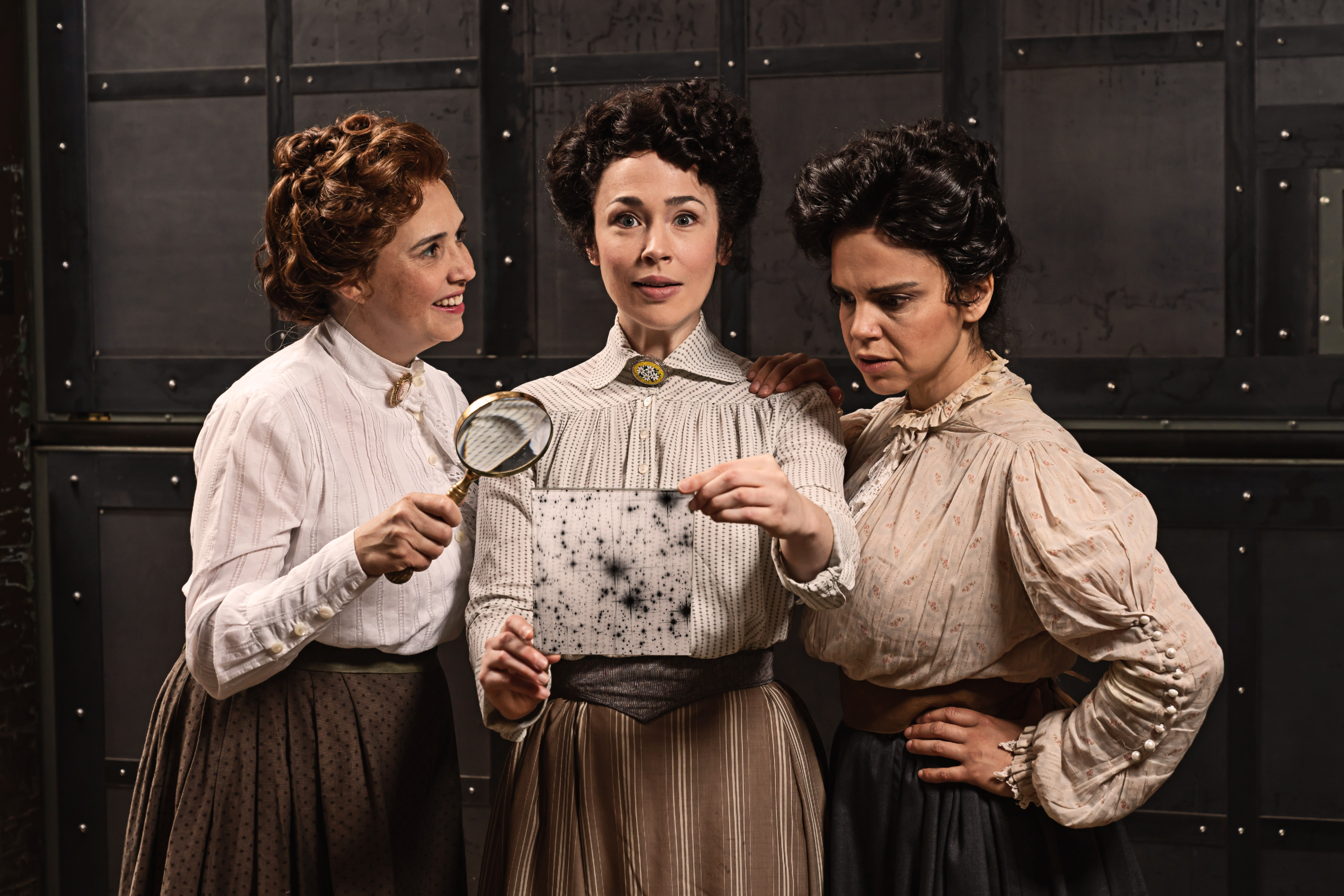 Three actresses wearing Victorian blouses and high-waisted skirts stand together. The woman in the middle holds a glass plate with a photograph of the night sky and has an expression of discovery on her face. The woman on the left holds a magnifying glass and smiles as she looks at the woman in the middle. The woman on the right stares at the details on the glass plate.