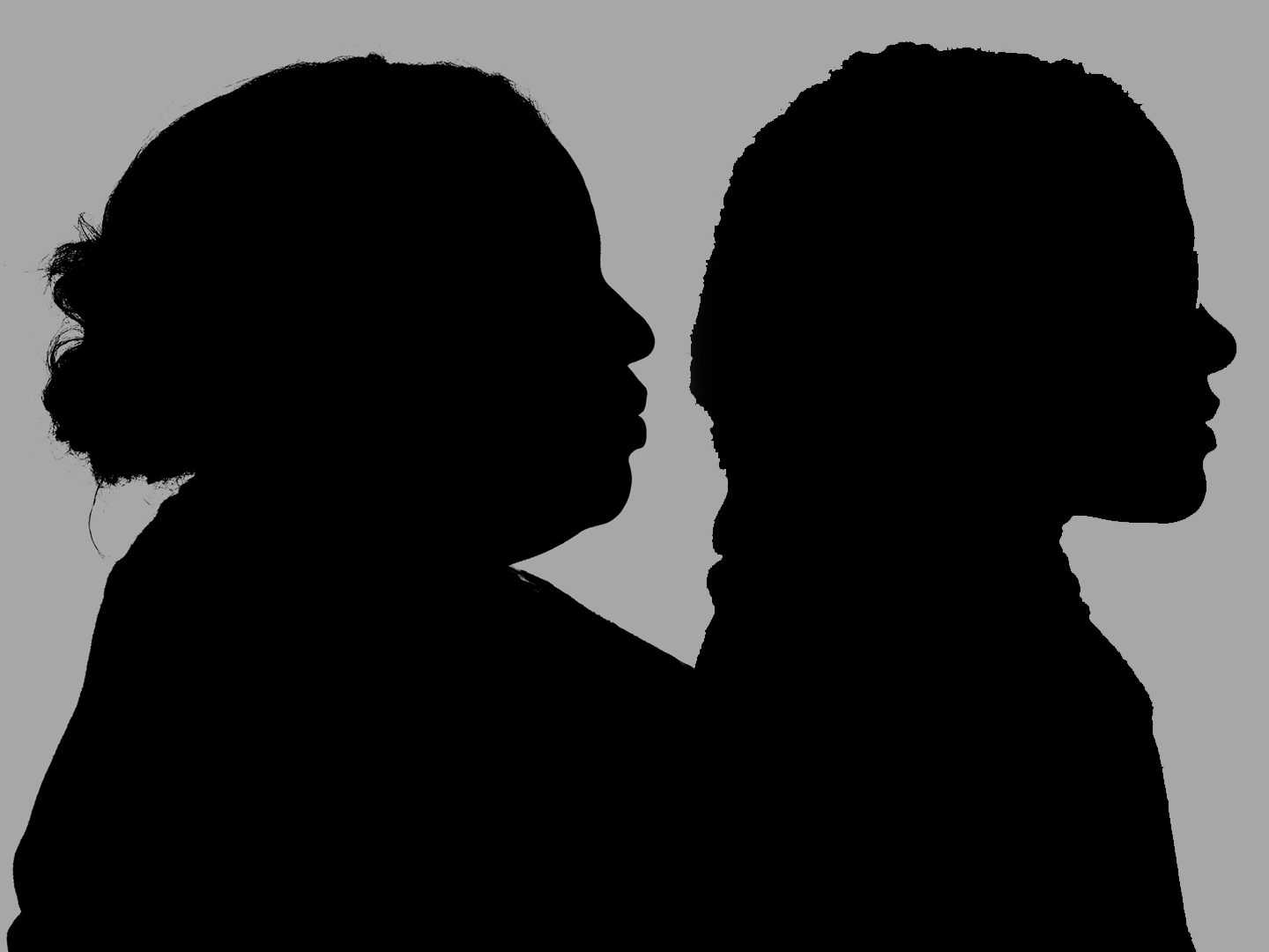 Silhouette of two Black women against a gray background.
