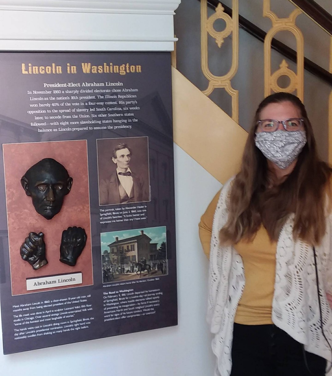Taryn stands next to a museum panel showing a life mask of Abraham Lincoln.