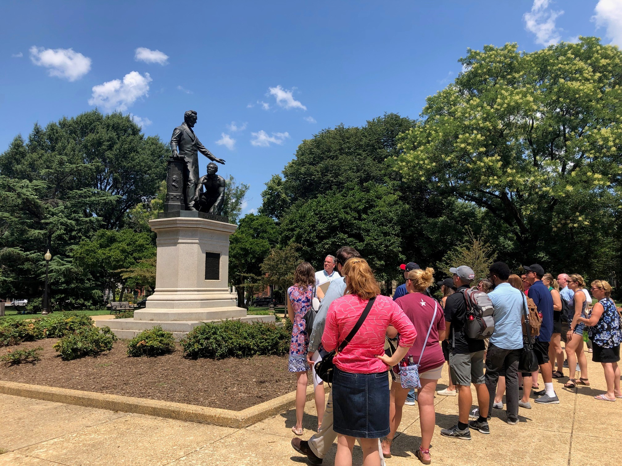 Teachers stand on DC's Lincoln's Park observing a statue of Abraham Lincoln and an emancipated slave. Lincoln stands and the emancipated man kneels beside him.