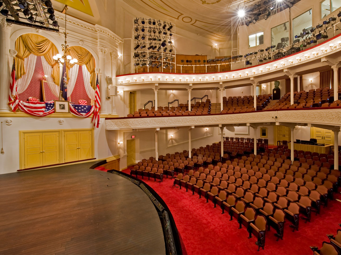 A side view of the stage and seating at Ford's Theatre. On the left is the President Box with an American flag, a framed picture of George Washington and American flag bunting draped over the box.