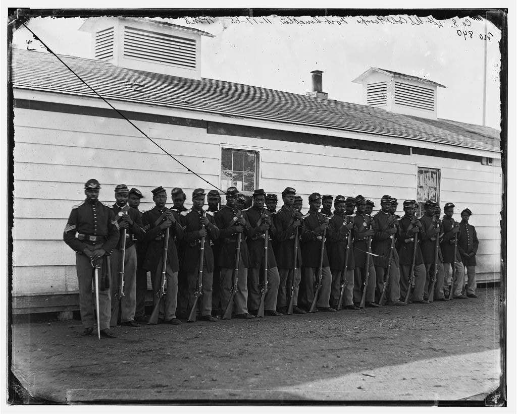 26 black Union soldiers in uniform stand in front of a building